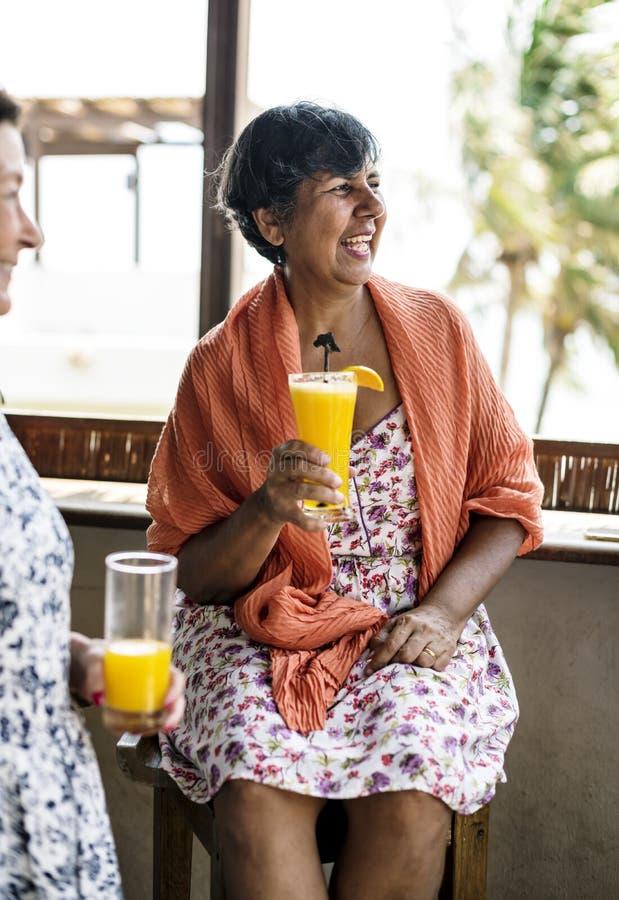 Hög kvinna som dricker orange fruktsaft på en semesterort royaltyfria bilder