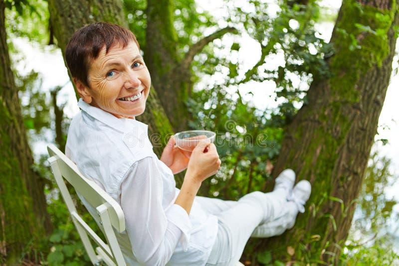 Hög kvinna som dricker te i natur arkivbild