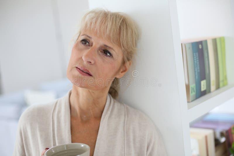 Hög kvinna som dricker te och att tänka arkivfoto