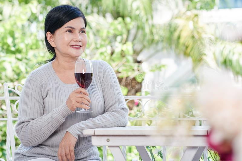 Hög kvinna som dricker vin royaltyfri foto