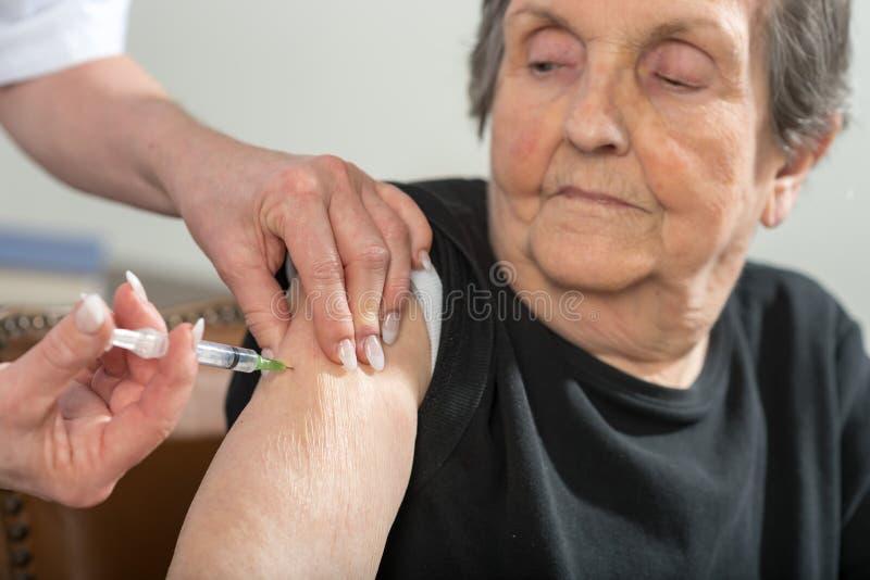 Hög kvinna som får en injektion royaltyfri fotografi