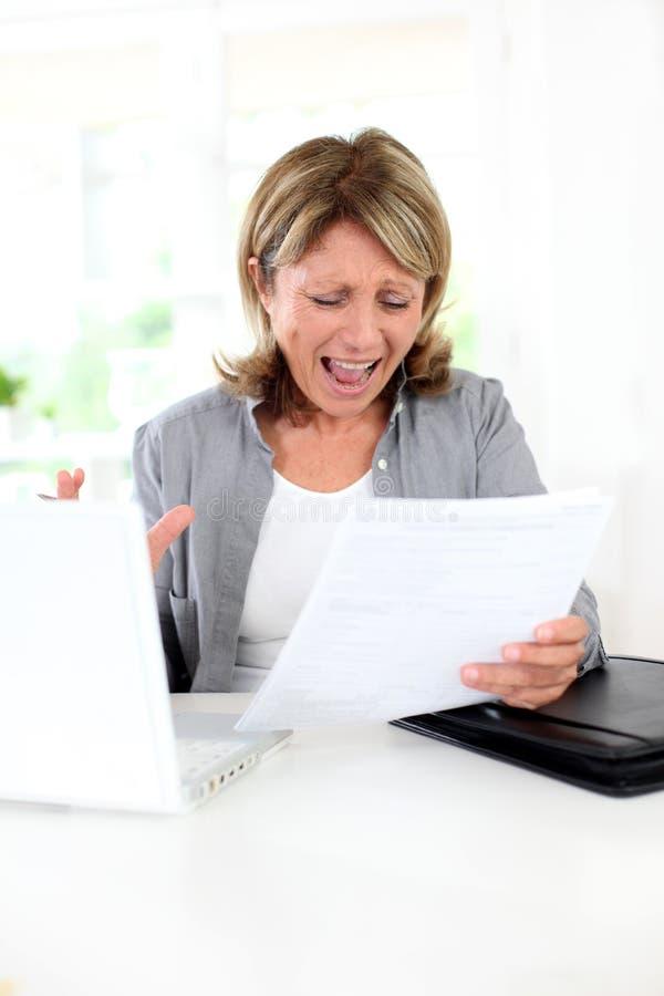 Hög kvinna som får galen med skrivbordsarbete royaltyfri fotografi