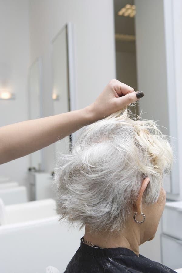 Hög kvinna som får henne hår gjort i salong arkivfoto