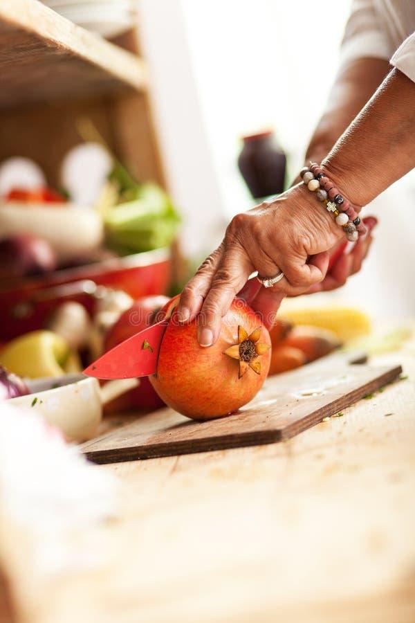 Hög kvinna som förbereder fruktsallad royaltyfri foto