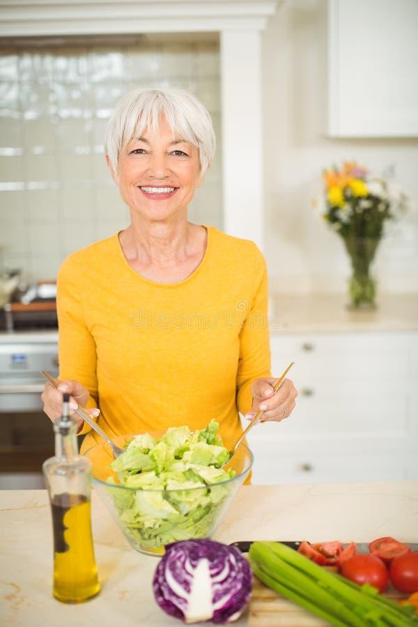 Hög kvinna som förbereder grönsaksallad royaltyfria bilder
