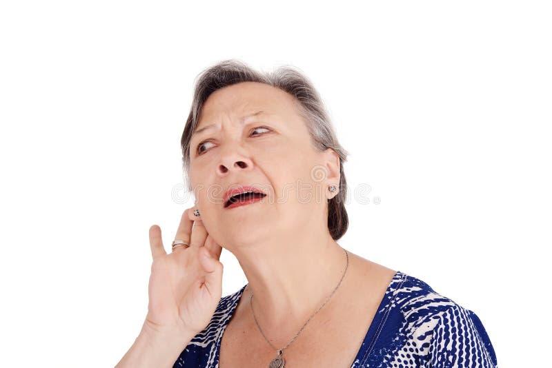 Hög kvinna som försöker att lyssna något royaltyfri foto