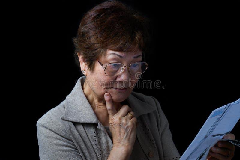 Hög kvinna som förvånas av hennes finansiella räkningar på svart backgroun royaltyfri bild