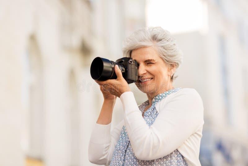 Hög kvinna som fotograferar vid den digitala kameran arkivbilder