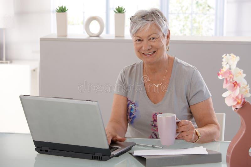 Hög kvinna som fungerar på att le för bärbar dator arkivfoton