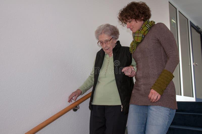 Hög kvinna som går ner trappa med portionhänder av den unga kvinnan royaltyfria foton