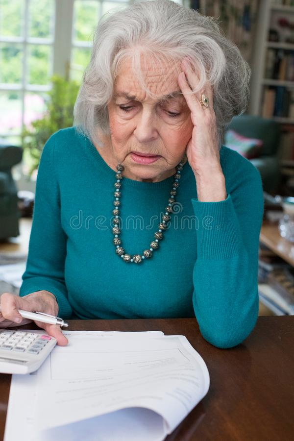 Hög kvinna som går till och med räkningar och ser oroad royaltyfria foton