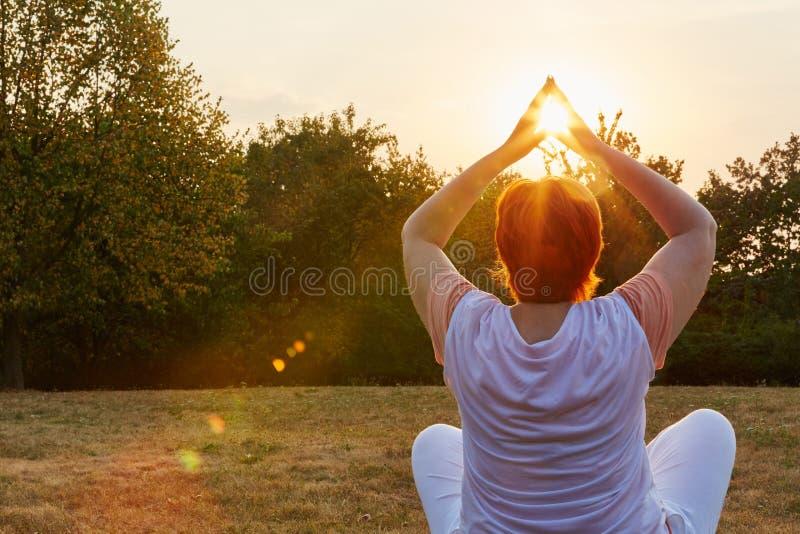 Hög kvinna som gör en yogaövning fotografering för bildbyråer