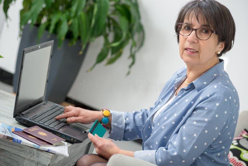 Hög kvinna som gör online-shopping arkivfoto