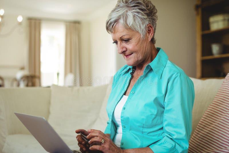 Hög kvinna som gör online-shopping på bärbara datorn royaltyfri bild