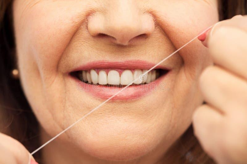 Hög kvinna som gör ren hennes tänder förbi tandtråd royaltyfria foton