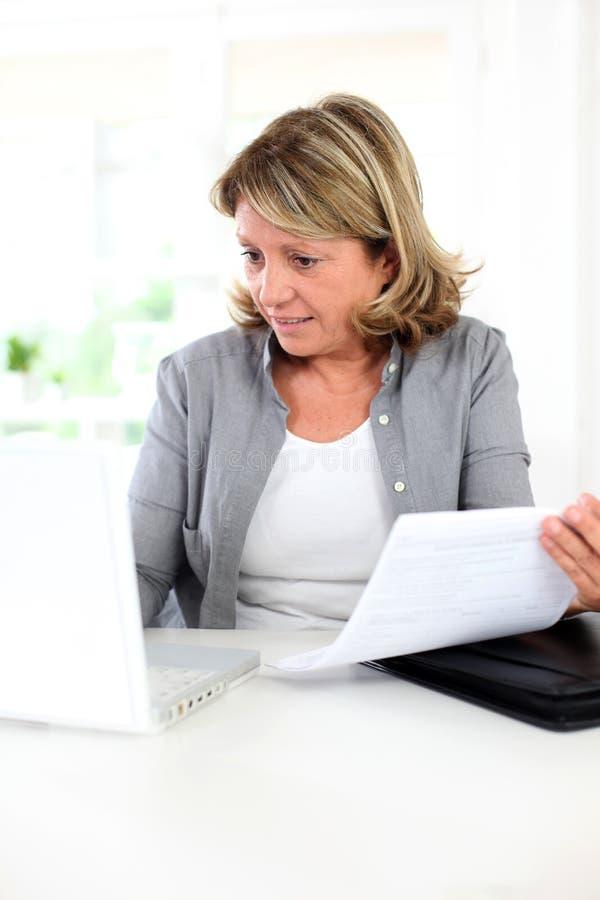 Hög kvinna som gör skrivbordsarbete på internet royaltyfri fotografi