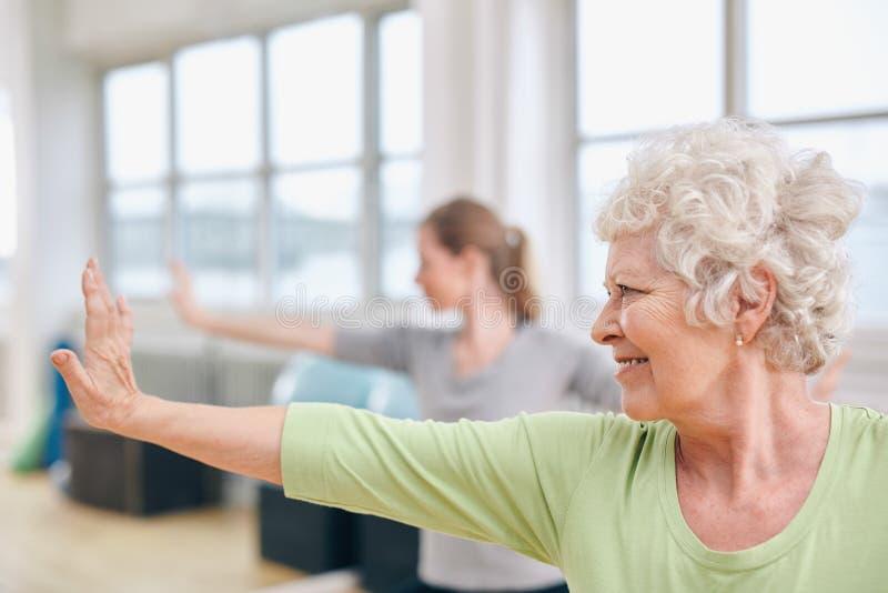 Hög kvinna som gör sträcka övning på yogagrupp royaltyfria bilder
