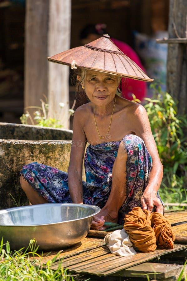 Hög kvinna som gör tvätterit i den Hsipaw byn, Myanmar royaltyfria foton