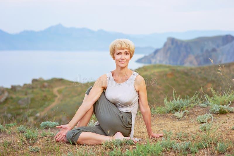 Hög kvinna som gör yogaövningar fotografering för bildbyråer