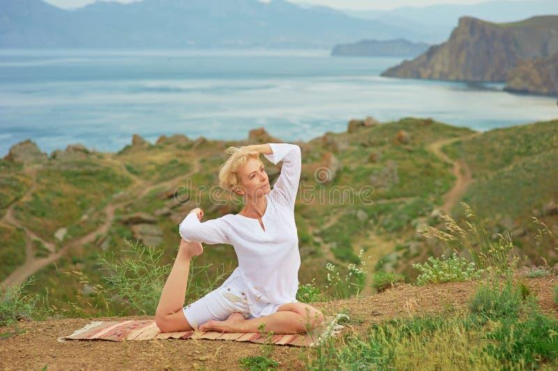 Hög kvinna som gör yogaövningar arkivfoto