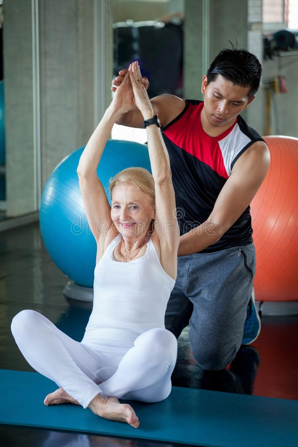 Hög kvinna som gör yoga i konditionidrottshall åldrig dam som övar den personliga instruktörmannen r Mogen sportutbildning arkivbild