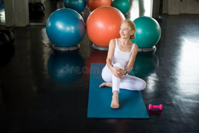Hög kvinna som gör yoga i konditionidrottshall r Gammal kvinnlig som tar ett avbrott från genomkörare Mogen sportutbildning royaltyfria bilder