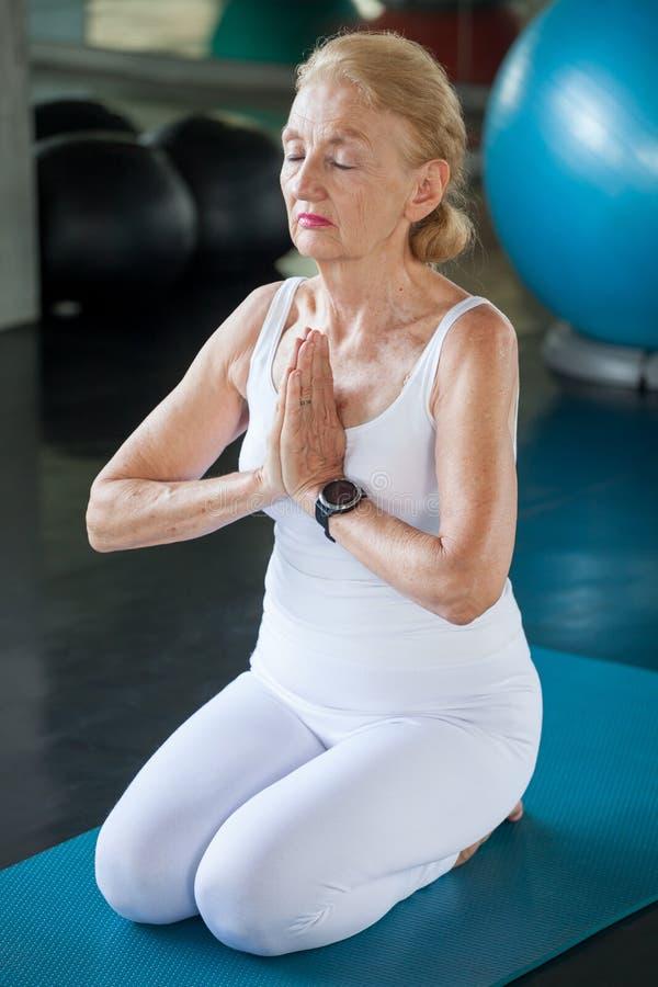 Hög kvinna som gör yoga i konditionidrottshall r r Mogen sportutbildning rehabilitering ?ldring royaltyfria bilder