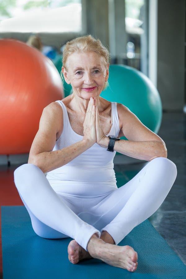 Hög kvinna som gör yoga i konditionidrottshall r r Mogen sportutbildning rehabilitering ?ldring arkivbilder