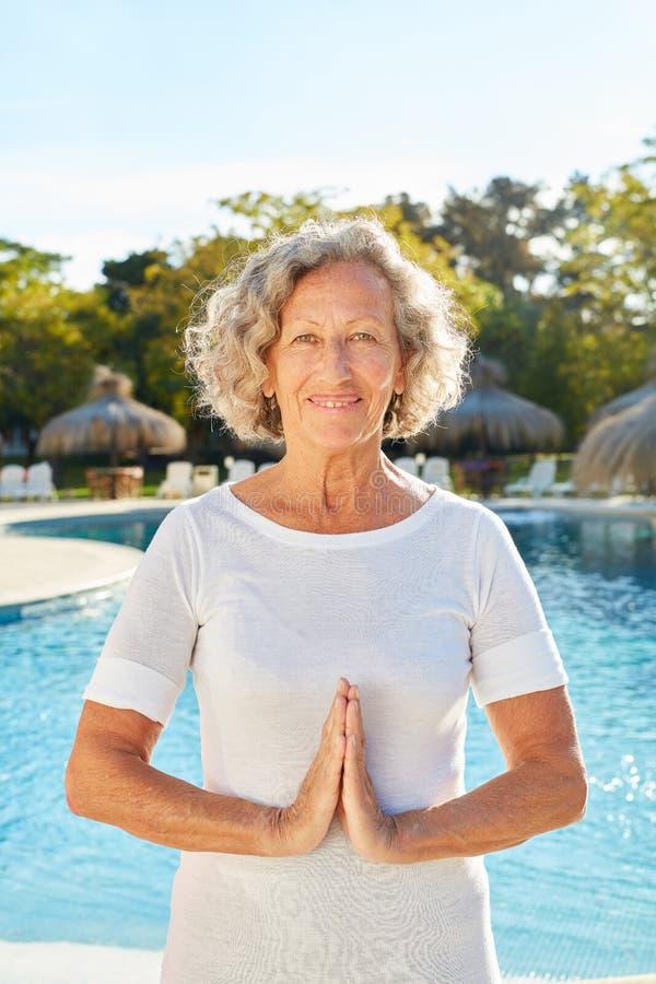 Hög kvinna som gör yogameditation vid pölen royaltyfri fotografi