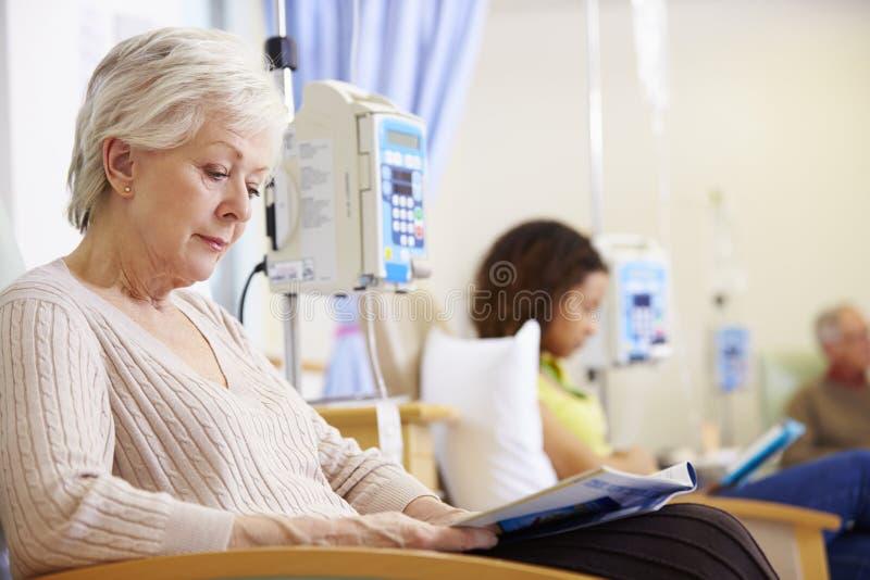 Hög kvinna som genomgår kemoterapi i sjukhus arkivfoton
