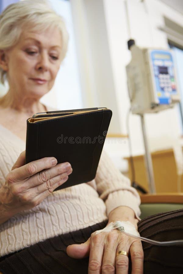 Hög kvinna som genomgår kemoterapi med den Digital minnestavlan royaltyfria foton