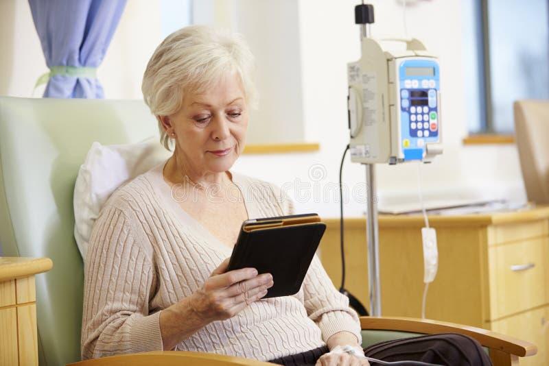 Hög kvinna som genomgår kemoterapi med den Digital minnestavlan arkivbild