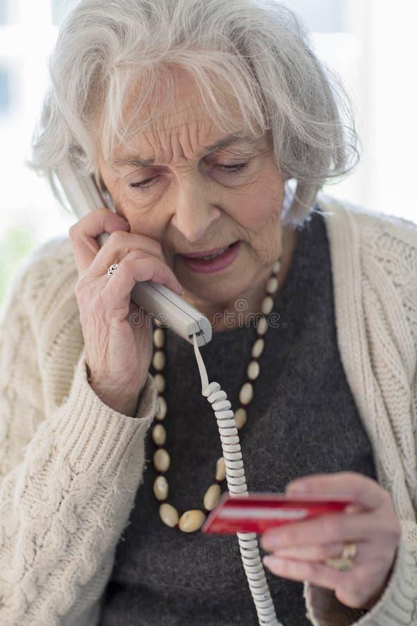 Hög kvinna som ger kreditkortdetaljer på telefonen arkivfoto