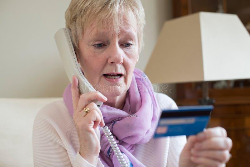 Hög kvinna som ger kreditkortdetaljer på telefonen royaltyfri fotografi