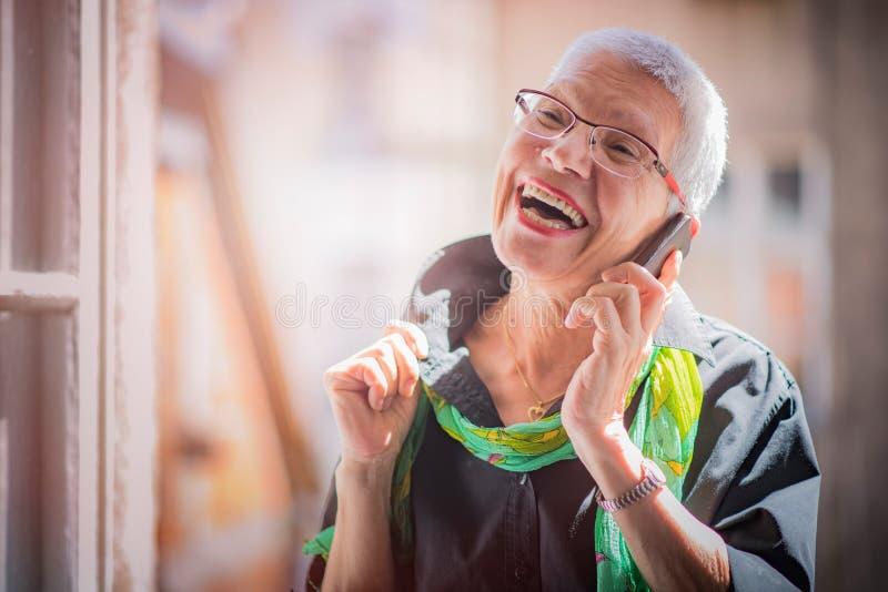 Hög kvinna som har ett älskvärt telefonsamtal royaltyfri foto