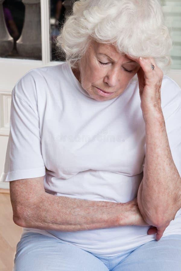 Hög kvinna som har huvudvärk arkivfoton