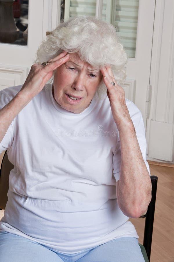 Hög kvinna som har huvudvärk fotografering för bildbyråer