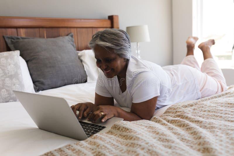 Hög kvinna som hemma använder bärbara datorn i sovrum arkivfoton