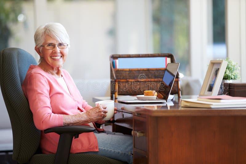 Hög kvinna som hemma använder bärbara datorn på skrivbordet royaltyfri fotografi