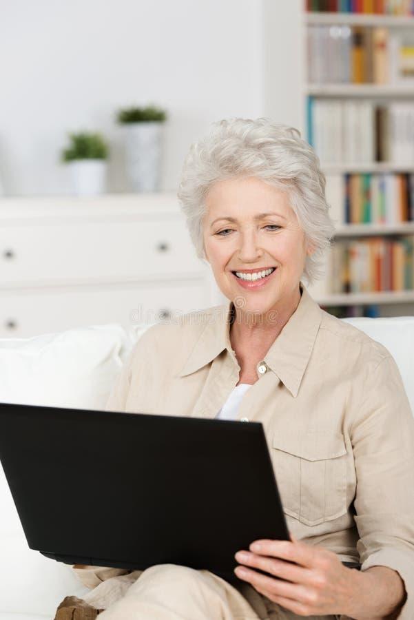 Hög kvinna som hemma använder en bärbar dator royaltyfria bilder