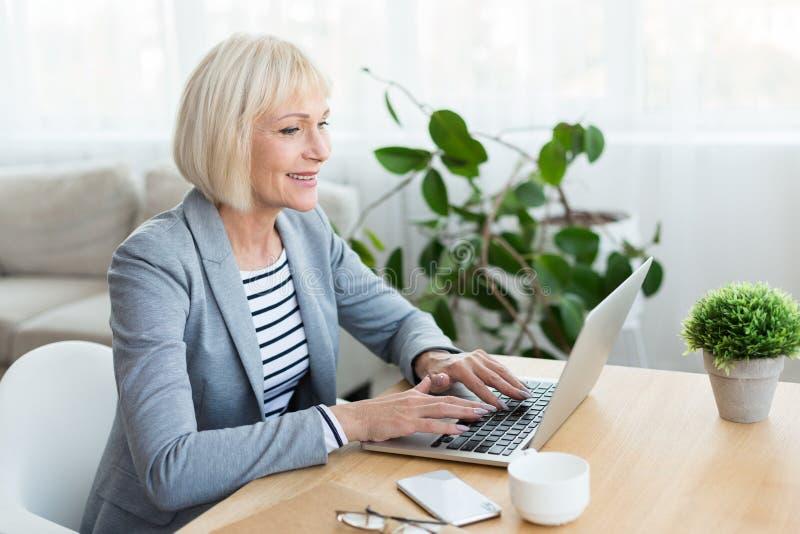 Hög kvinna som hemma arbetar på bärbar datordatoren royaltyfri fotografi