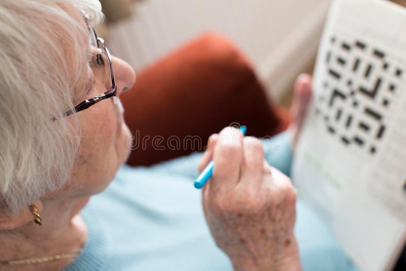 Hög kvinna som hemma gör korsordpusslet fotografering för bildbyråer