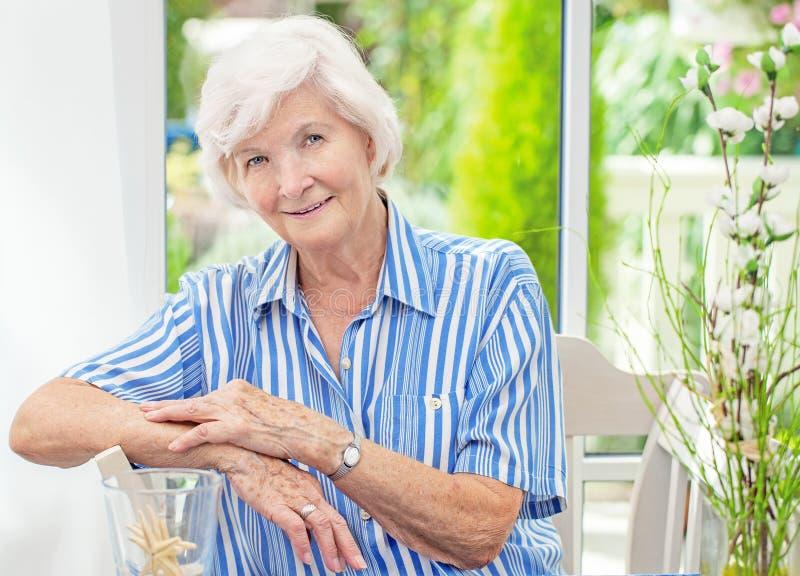 Hög kvinna som hemma sitter royaltyfria foton