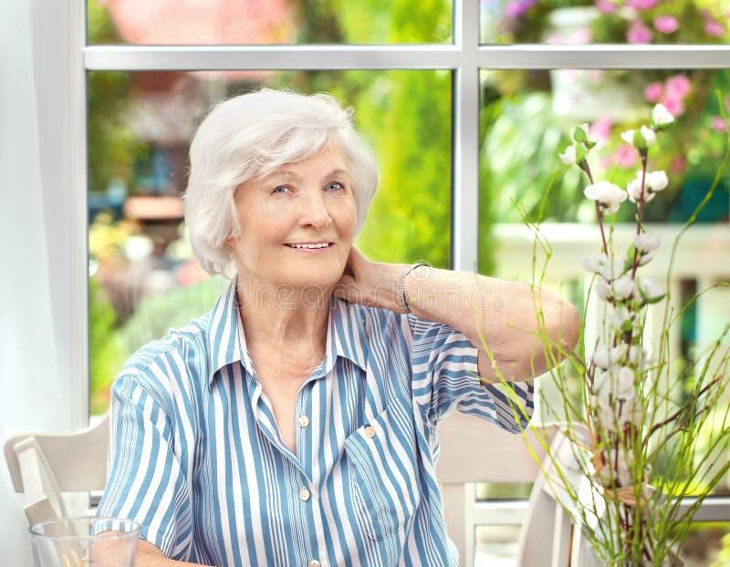 Hög kvinna som hemma sitter 5 arkivbild