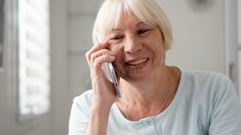 Hög kvinna som hemma sitter genom att använda smartphonen Pensionerad kvinna som talar på mobiltelefonen arkivbild