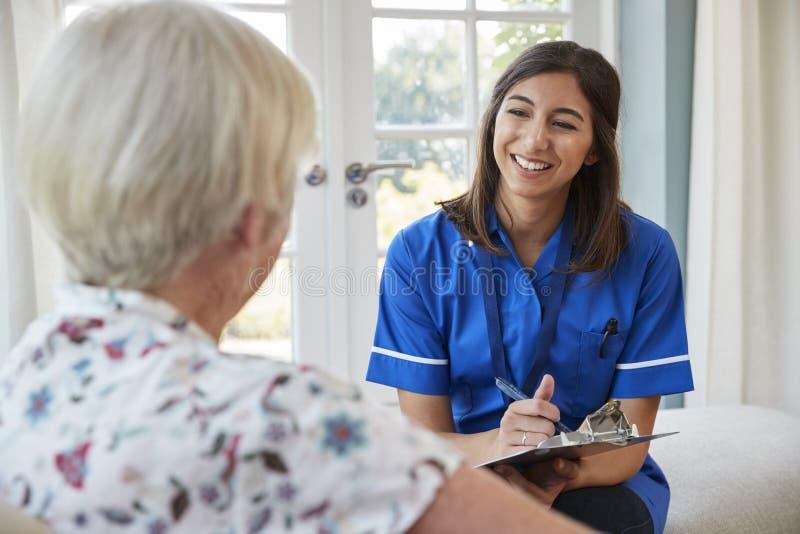 Hög kvinna som hemma sitter med omsorgsjuksköterskan som tar anmärkningar arkivfoto