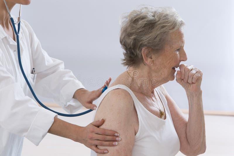 Hög kvinna som hostar medan doktor Examining Her royaltyfri foto