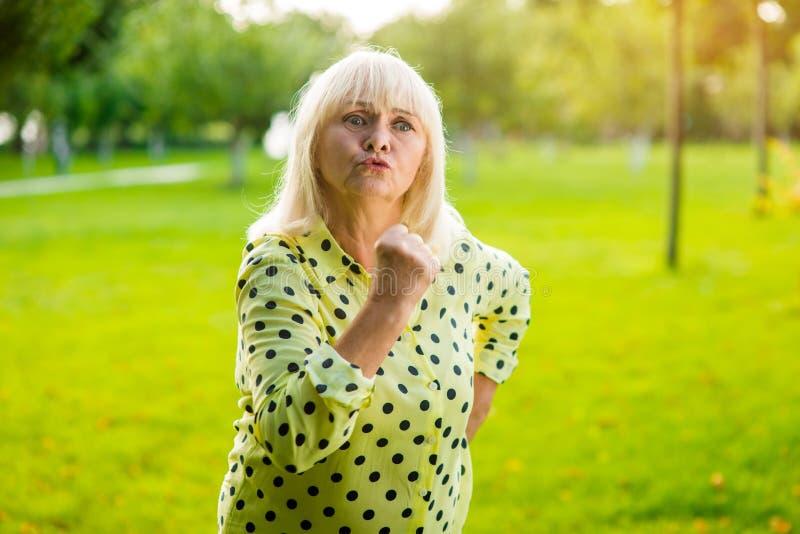 Hög kvinna som hotar med näven royaltyfri foto