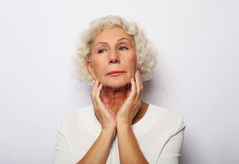 Hög kvinna som känslablått oroade om problem, eftertänksam uppriven ledsen mitt, åldrades den gråa haired damen royaltyfri bild