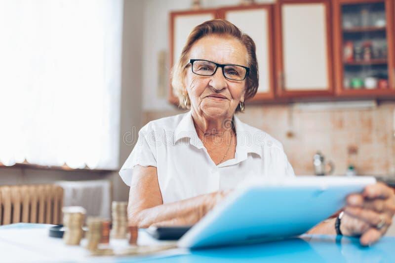 Hög kvinna som kontrollerar henne finanser och invenstments royaltyfria foton